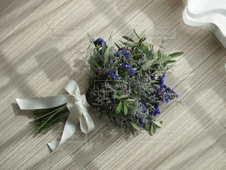 木製テーブルの上に座っている花の花瓶の写真・画像素材[1653542]