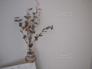 テーブルの上に座っての花で一杯の花瓶の写真・画像素材[1853858]