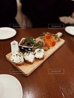 木製のテーブルの上に座っているピザのスライスの写真・画像素材[2713710]