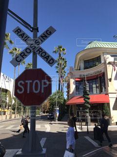 一時停止の標識の前の通りを渡る人々 のグループの写真・画像素材[1594648]