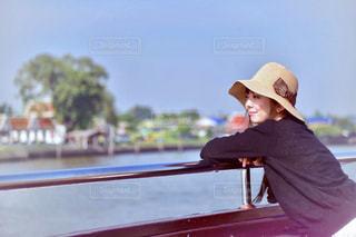 水の体の横にあるベンチに座っている人の写真・画像素材[1135614]