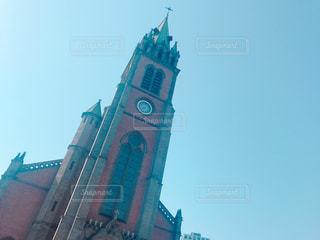 建物の上部に時計と大きな背の高い塔 - No.1188555