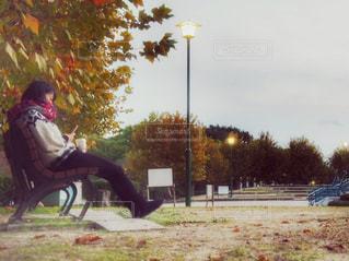 公園のベンチに座っている人の写真・画像素材[873323]