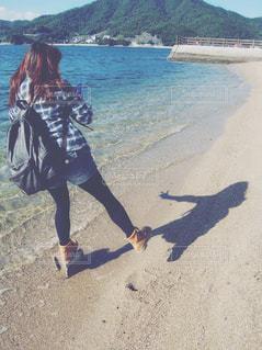 綺麗な海と影遊びをする女性の写真・画像素材[885818]