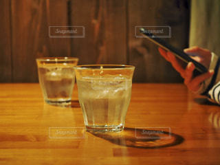 テーブルの上に水の入ったグラスの写真・画像素材[1082245]
