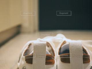 玄関に置いてある白スニーカーの写真・画像素材[1130003]