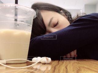テーブルでうたた寝する女性の写真・画像素材[1158524]