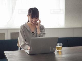 パソコンで作業をしながら電話をする女性の写真・画像素材[1166430]