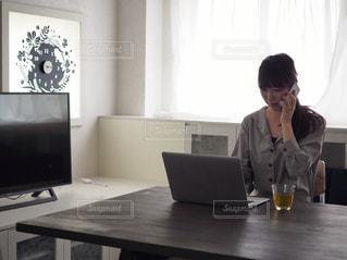 ノートパソコンで作業しながら電話をする人の写真・画像素材[1166431]