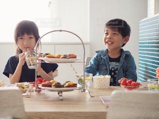 飲み物を飲む女の子と、ポップコーンを食べる男の子の写真・画像素材[1166625]