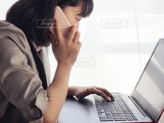 電話をしながら、ラップトップ コンピューターを使用している人の写真・画像素材[1191108]