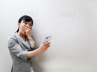 思わぬ通知に驚く女性の写真・画像素材[1206011]
