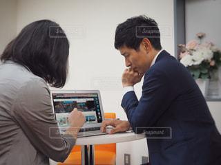 パソコンを見ながら相談中の男女の写真・画像素材[1206012]