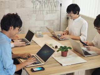 ラップトップを使用してテーブルに座っている人々 のグループの写真・画像素材[1321744]
