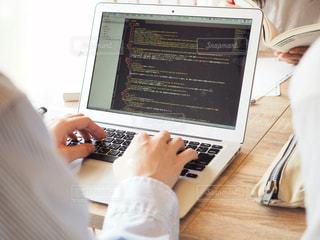 机の上に座っているラップトップ コンピューターを使用している人の写真・画像素材[1322634]