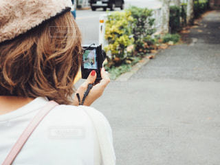 写真を撮っている帽子をかぶった女性の写真・画像素材[1536586]