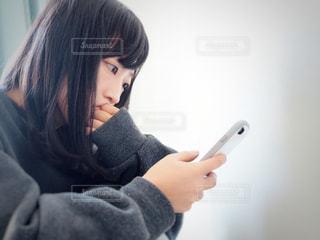 部屋でスマホをいじる女性の写真・画像素材[1588629]
