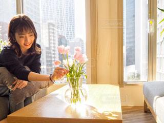 窓の前のテーブルに座っている女性の写真・画像素材[1821141]