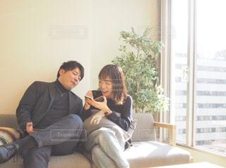 スマホをのぞきこむカップルのひとコマの写真・画像素材[1821143]