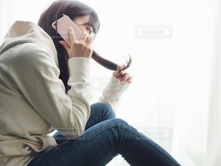 電話中に枝毛チェックする女性の写真・画像素材[1822247]