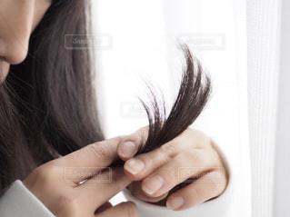 髪の傷みをチェックする女性の写真・画像素材[1822330]