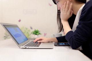 ラップトップコンピュータを使ってテーブルに座っている女性の写真・画像素材[2272725]