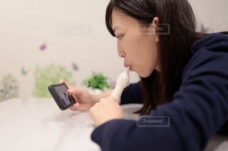 パピコを食べながらスマホを見ている女性の写真・画像素材[2272731]