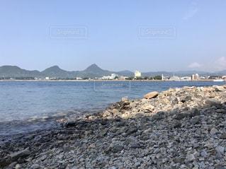 水の体の横にある岩のビーチの写真・画像素材[709871]