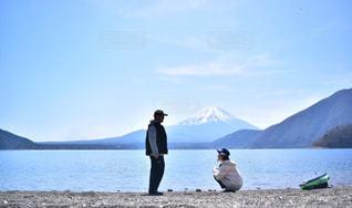 水の体の前で立っている人のカップルの写真・画像素材[856472]
