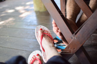 木製のベンチに座っている人の写真・画像素材[930351]