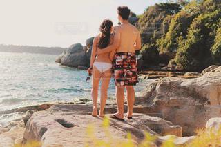 水の体の横にある岩の上に立っている人の写真・画像素材[1234048]