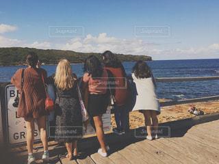 水の体の横に立っている人のグループの写真・画像素材[1234089]