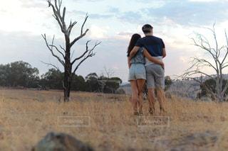 乾いた草のフィールドに立っている人の写真・画像素材[1234128]