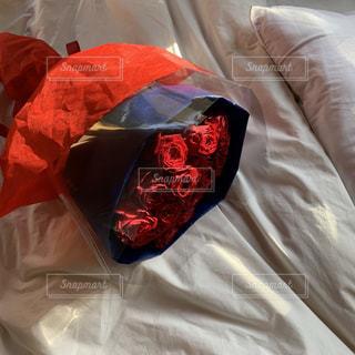 赤い毛布が付いたベッドの写真・画像素材[2432337]