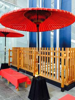赤い傘の前に座っている椅子の写真・画像素材[717619]