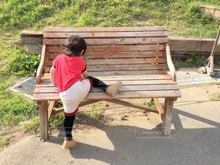木製のベンチに座っている少年の写真・画像素材[1126630]