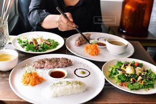 食品のプレートをテーブルに座っている女性の写真・画像素材[1511354]