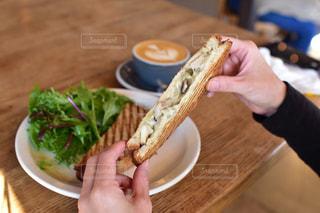 テーブルに食べ物のプレートを持っている人の写真・画像素材[1660496]