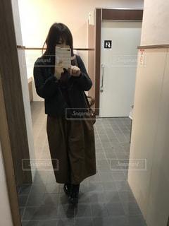 カメラにポーズ鏡の前に立っている人の写真・画像素材[1010626]