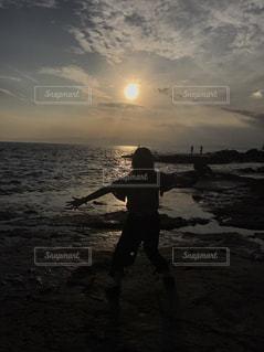 バック グラウンドで夕焼けのビーチに立っている人の写真・画像素材[755950]