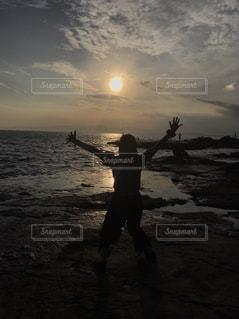 バック グラウンドで夕焼けのビーチに立っている人の写真・画像素材[755951]
