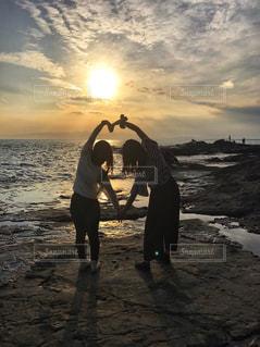 バック グラウンドで夕焼けのビーチに立っている人の写真・画像素材[755969]