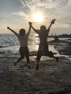 浜辺でフリスビーをキャッチする空気に飛び込む女性の写真・画像素材[755972]