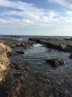 水の体の横にある岩のビーチの写真・画像素材[756012]