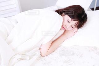 ベッドの上で横になっている人の写真・画像素材[1031654]