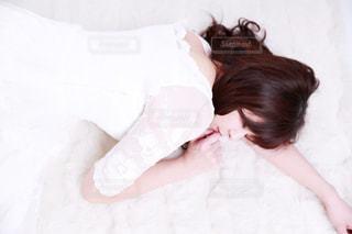 ベッドの上で横になっている少女の写真・画像素材[1031655]
