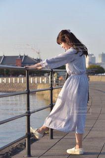 フェンスの前に立っている人の写真・画像素材[1587296]