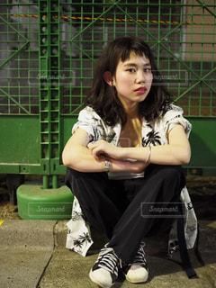 フェンスの前にあるベンチに座っている女性 - No.708272