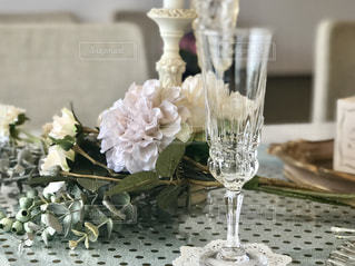 グラスワインの隣に座っている花で満たされた花瓶の写真・画像素材[2103081]