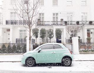 雪の中、建物の前に停まっている車の写真・画像素材[1033103]